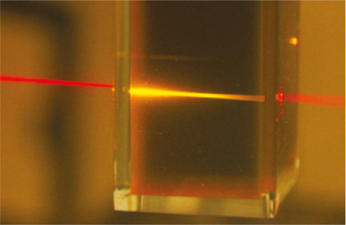 Red light from a laser pointer is converted into higher-energy yellow<br />light as it passes through the liquid photochemical upconverter.<br />Source: University of Sydney, Australia