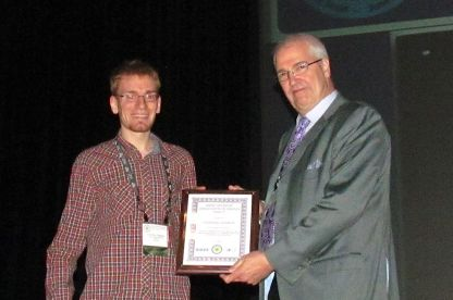 Dominic (right) receives the IEEE PVSC Award from the Conference Chair B.J. Stanberry (left).