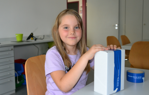 <p>Maxi W., 6 years old, is happy about her homemade spectroscope, which she could take home with her.</p>