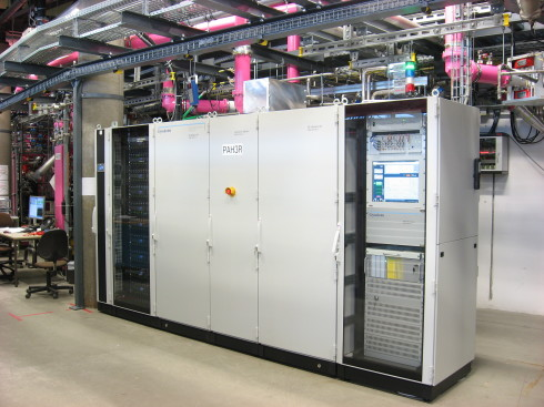 <p>One of the new solid state transmitters: the power supplies are located in the left rack (black), the RF section is located behind the grey doors in the middle and in the right rack the control units can be seen.</p>