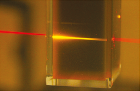 <p>Red light from a laser pointer is converted into higher-energy yellow<br />light as it passes through the liquid photochemical upconverter.<br />Source: University of Sydney, Australia</p>